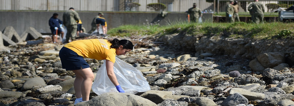 Master-at-Arms 1st Class Michelle Marcial, assigned to Fleet Activities (FLEACT) Yokosuka's security department, cleans up debris from the shoreline surrounding the FLEACT Yokosuka helipad. FLEACT Yokosuka provides, maintains, and operates base facilities and services in support of the U.S. 7th Fleet's forward-deployed naval forces, 71 tenant commands, and more than 27,000 military and civilian personnel. (U.S. Navy photo by Mass Communication Specialist 2nd Class Tyler R. Fraser/Released)