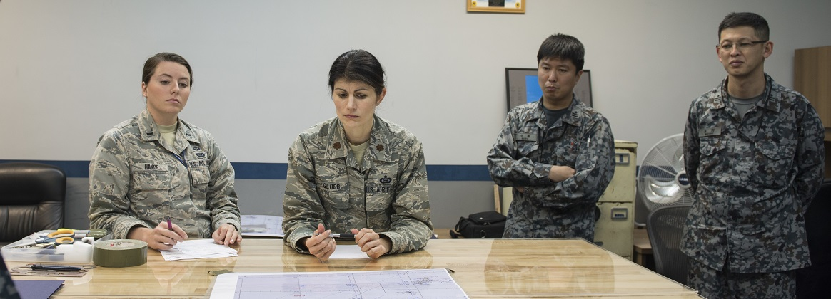 Japan Air Self Defense Force officers and their United States Air Force counterparts discuss the outcome of their bilateral exchange Jan. 11, 2018, at Kadena Air Base, Japan. Both JASDF and USAF members gained valuable knowledge from the bilateral exchange.